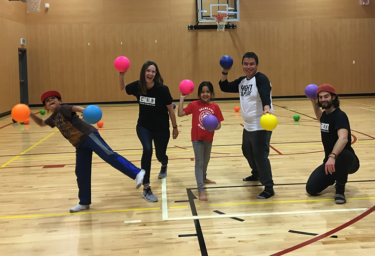 A group of children and staff ready to play dodgeball in a gymnasium.