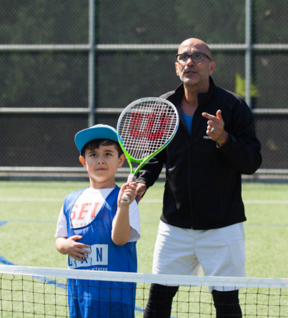 A child prepares to hit a tennis ball with his racket under the guidance of a coach.