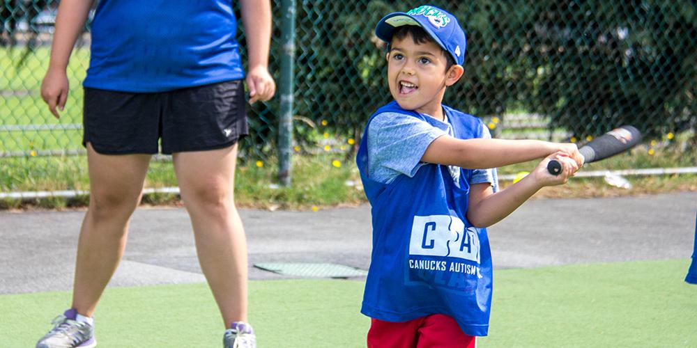 A young boy swings a baseball bat in an outdoor field.