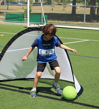 A boy kicks a soccer ball on an outdoor field.