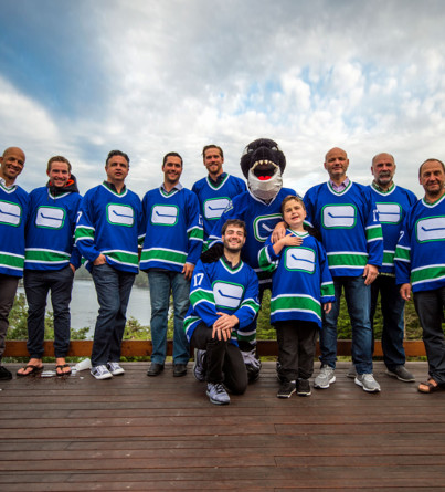 A group of men in hockey jerseys pose for a photo on a patio deck.