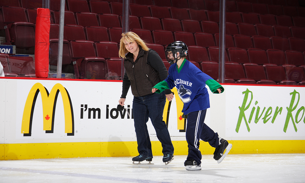 A mother and son ice skate together.