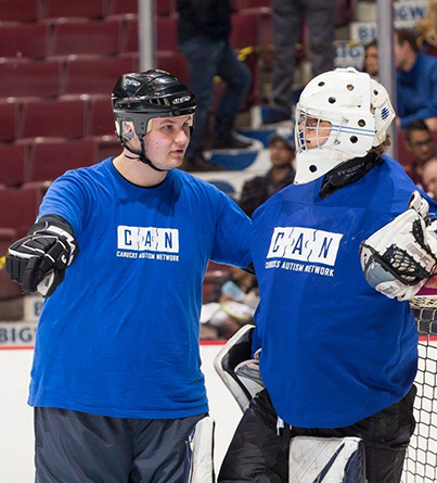 A male coach talking with an ice hockey goalie on the ice.