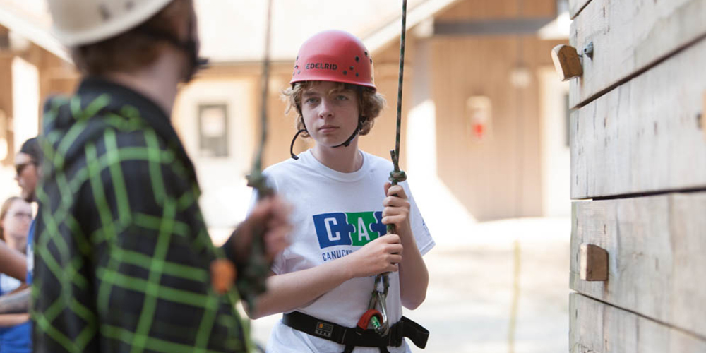 A youth male at a rock climbing wall