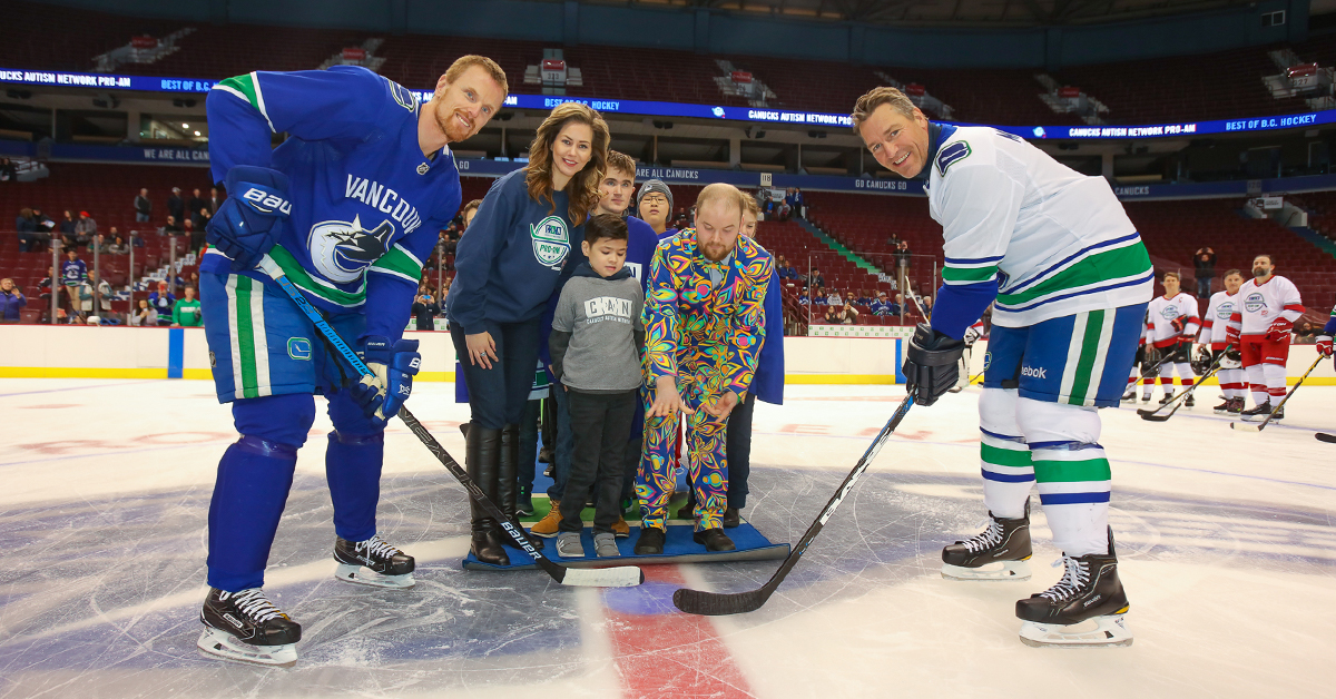 Vancouver Canucks Alumni Daniel Sedin and Kirk McLean with representatives from the Canucks Autism Network at a ceremonial puck drop at Rogers Arena