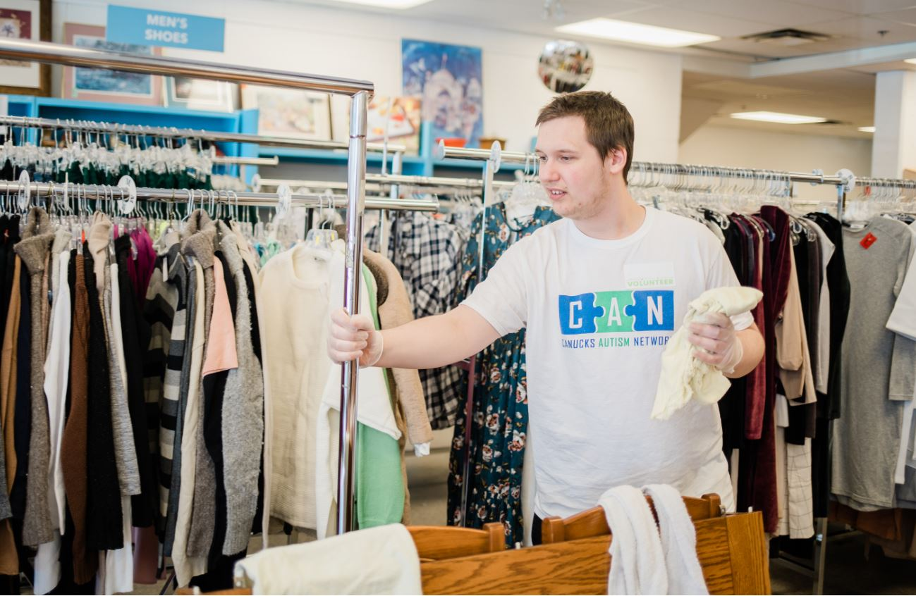 A male young adult organizes a clothing rack at a thrift store