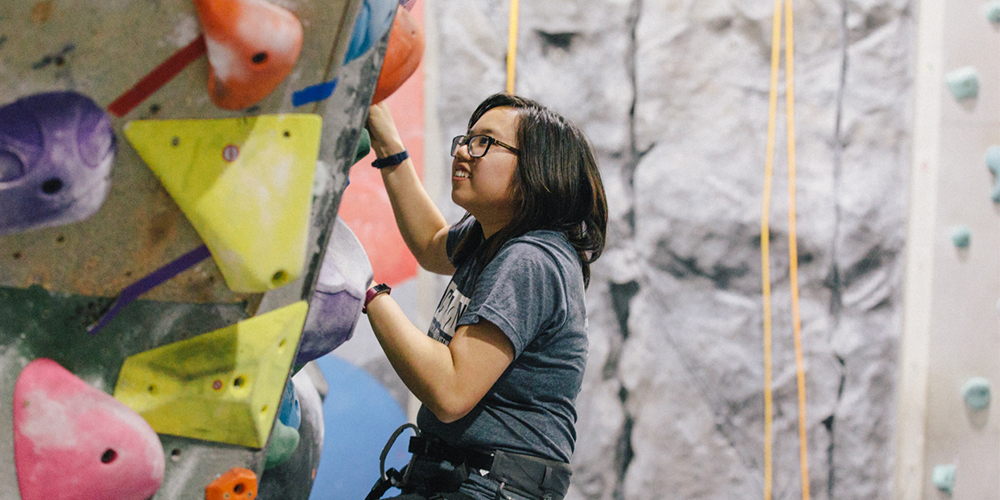 A young adult woman rock climbing