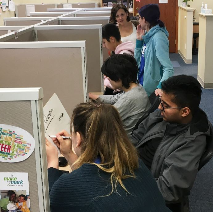 Six youth and young adults work in pairs at computer cubicles