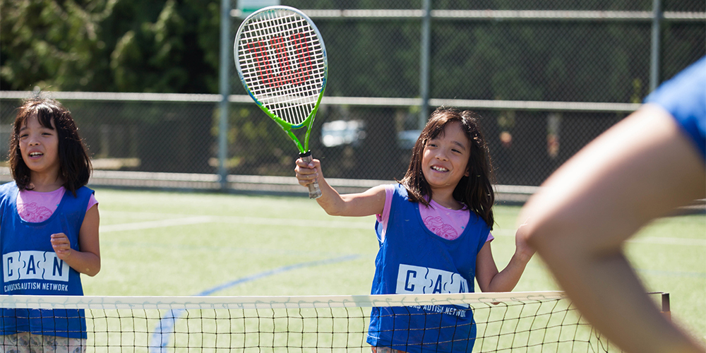 A girl prepares to hit a tennis ball with her racket.