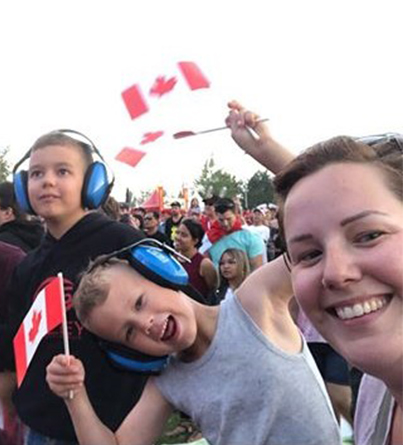 Family at a Canada Day celebration with Canadian flags and noise-cancelling headphones
